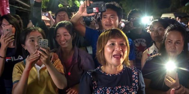 最後に助けられた少年が乗った救急車が病院に到着すると、集まった多くの人たちが喜びの声をあげた=7月10日、タイ・チェンライ