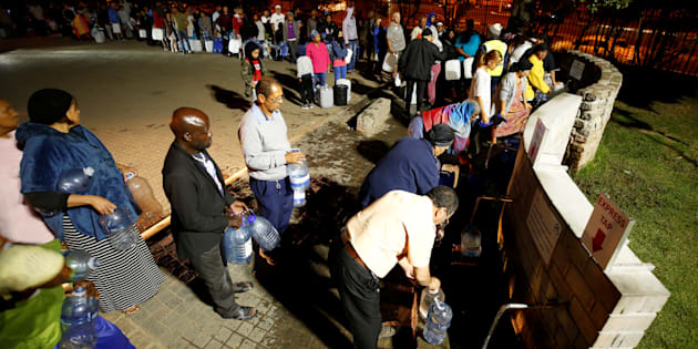 People queue to collect water from a spring in the Newlands suburb as fears over the city's water crisis grow in Cape Town.