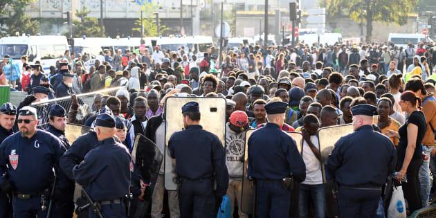 Des policiers font face aux migrants pendant l'évacuation d'un camp sauvage à la porte de la Chapelle à Paris, le 7 juillet.