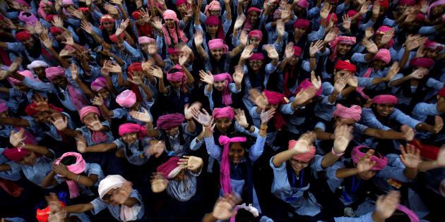 Miles de niñas uniformadas esperan su turno para entrar a su escuela.