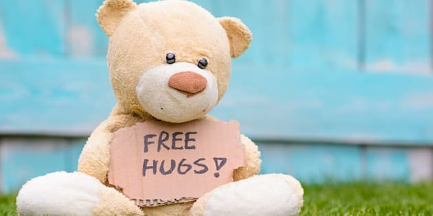 Little old teddy bear sitting on the grass in the garden and holding a piece of cardboard with the information - Free Hugs !