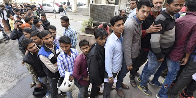 People stand in a queue outside banks to deposit and exchange old denomination Indian rupee 500 and 1000 currency notes, at Barakhamba Road, on November 24, 2016 in New Delhi, India.
