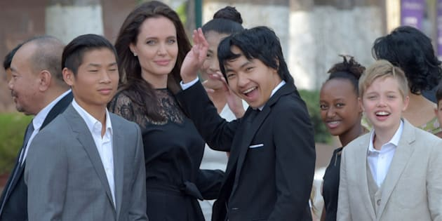 Angelina Jolie and her children gesture to media in front of the royal residence for a meeting with Cambodian King Norodom Sihamoni in Siem Reap on Feb. 18.