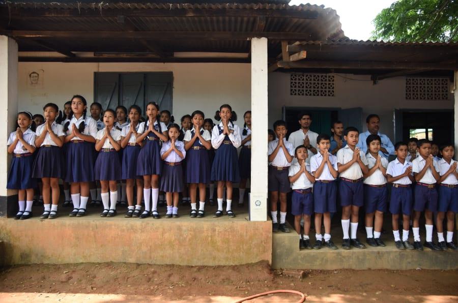 In this photograph taken on June 1, 2016, Indian schoolchildren take part in morning prayers at Rashtriya Swayamsevak Sangh(RSS)run Sankardev Sishu Nikatan School in the Betkuchi area of Guwahati.