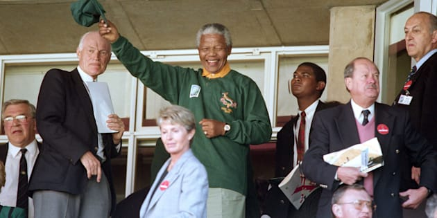 South African president Nelson Mandela wearing a Springbok jersey and cap waves upon arriving at Ellis Park in Johannesburg for the Rugby World Cup final on June 24 1995.
