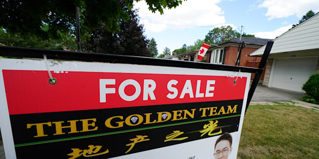 """A """"for sale"""" sign in the front yard of a house in Toronto, Ont., July 17. The Canada Mortgage and Housing Corporation says the country's housing sector is facing a high degree of vulnerability to market instability for the eighth straight quarter."""