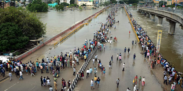 This general view shows Indian residents as they look at floodwaters on a major highway in Chennai on December 3, 2015.  Thousands of rescuers raced to evacuate residents from deadly flooding, as India's Prime Minister Narendra Modi went to the southern state of Tamil Nadu to survey the devastation. More than 40,000 people have been rescued in recent days after record rains lashed the coastal state, worsening weeks of flooding that has killed 269 people AFP PHOTO/STR / AFP / STRDEL        (Photo credit should read STRDEL/AFP/Getty Images)