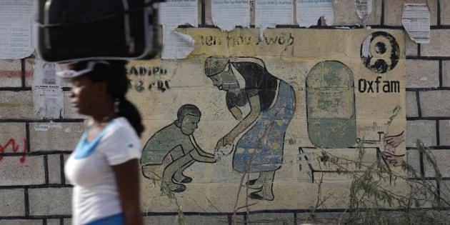 Una mujer pasa junto a un mural con el logo de Oxfam en Corail, Haití.