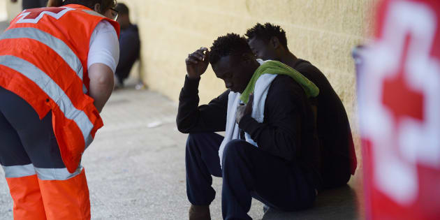 Un miembro de la Cruz Roja asiste a varios migrantes en la puerta de un gimnasio usado como centro de acogida este jueves, 21 de junio de 2018, en Jerez de la Frontera (Cádiz), donde llegaron cientos de migrantes en barco la semana pasada.