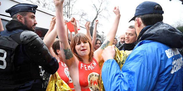 Un agent de sécurité privée au côté d'un CRS encadrant une manifestation perturbée par des militantes Femen.
