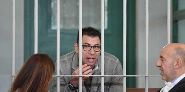 Valentino Talluto (C), an Italian HIV-positive man accused of infecting through unprotected sex about 30 women, speaks with lawyers Tiziana De Biase (L) and Maurizio Barca during his trial on October 25, 2017 in the courtroom of the Rebibbia prison.  / AFP PHOTO / Tiziana FABI        (Photo credit should read TIZIANA FABI/AFP/Getty Images)