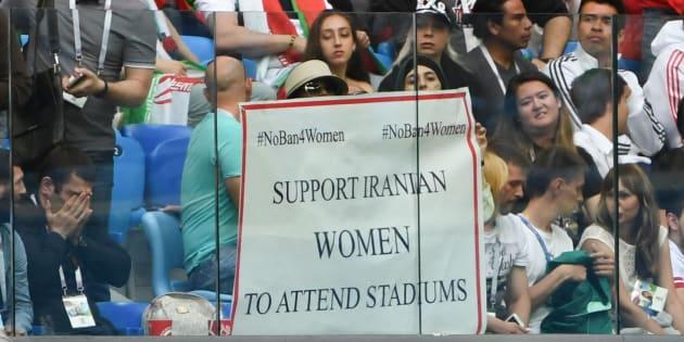 """Lors du match Iran-Maroc à Saint-Pétersbourg pour la Coupe du Monde le 15 juin 2018, des femmes brandissent une affiche où il est écrit """"Pas d'interdiction pour les femmes: Soutenez le droit des femmes iraniennes à assister aux matchs dans les stades""""."""