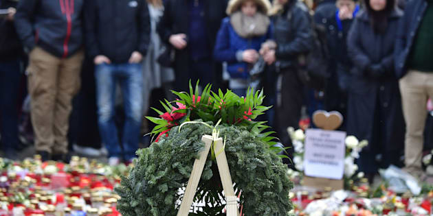 TOPSHOT - People mourn at a makeshift memorial for the victims of the Christmas market attack near the Kaiser-Wilhelm-Gedaechtniskirche (Kaiser Wilhelm Memorial Church) in Berlin on December 24, 2016. Germany hunts for possible accomplices of the suspected Berlin truck attacker Anis Amri, who was shot dead by Italian police in Milan on Friday, December 23, 2016. The Islamic State group has claimed responsibility for this week's attack on a Berlin Christmas market, in which 12 people were killed and dozens more wounded. / AFP / John MACDOUGALL        (Photo credit should read JOHN MACDOUGALL/AFP/Getty Images)