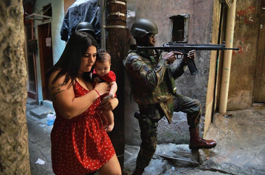 Mulher com bebê no colo na favela da Rocinha, no Rio de Janeiro, ocupada pelo Exército.