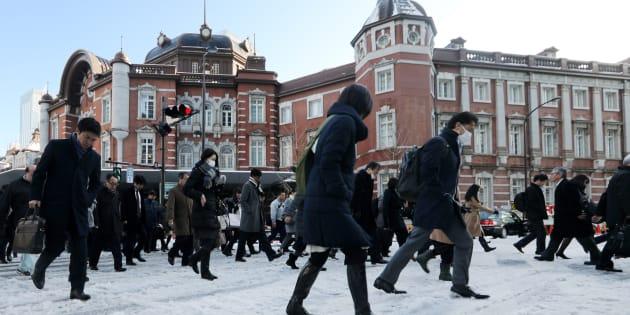 雪が積もった東京駅前の横断歩道を渡る通勤者ら=23日午前、東京都千代田区   撮影日:2018年01月23日