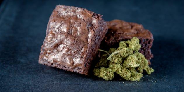 A stack of marijuana edible brownies next to a small pile of medical marijuana nugs. Black background