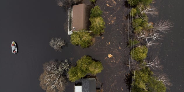 A boat drives next to cottages and homes along a flooded roadway on Grand Lake, N.B. as floodwaters continue to rise from the Saint John River on May 1, 2018.