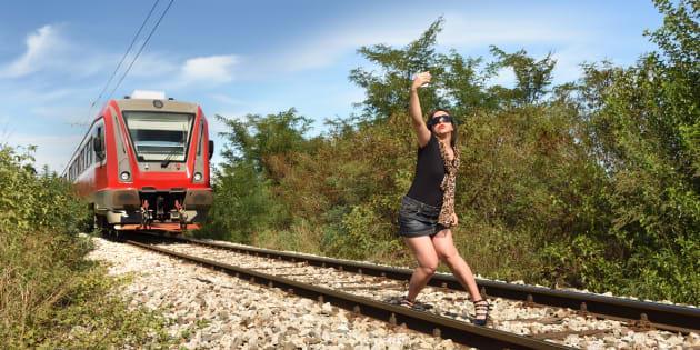 近づく列車の前で自撮りする女性(イメージ写真)