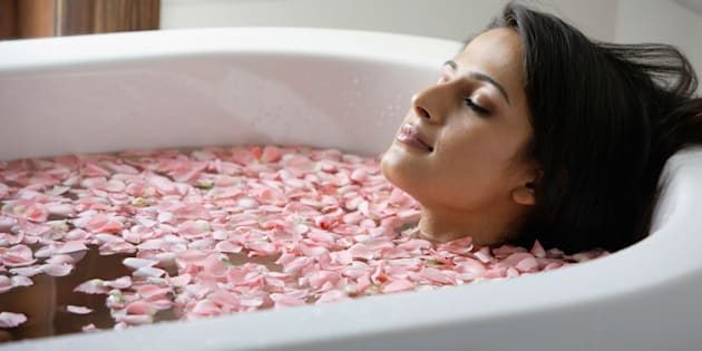 woman in tub with floating petals