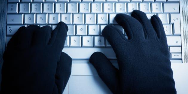 IT Crime consept Hacker works on laptop