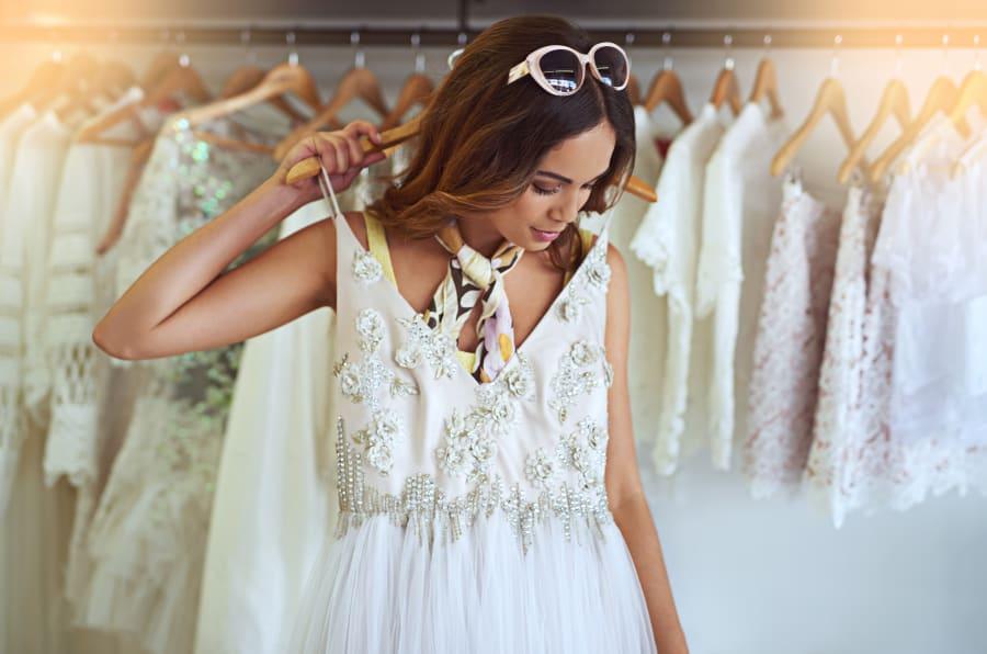 Imagen de una mujer probándose un vestido de novia.