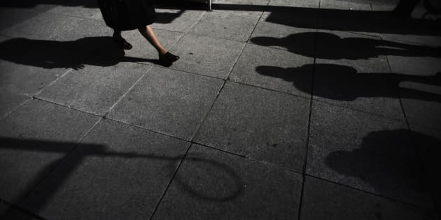 Shadows are seen as a woman walks down Bay Street in the financial district in Toronto, March 11, 2009.