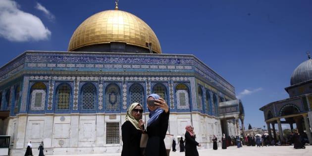 Deux palestiniennes se prennent en photo devant le Dome du rocher de la grande Mosquée Al Aqsa de Jérusalem.