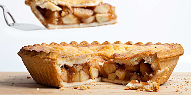 A whole apple pie with a slice removed and held overhead on a white background.
