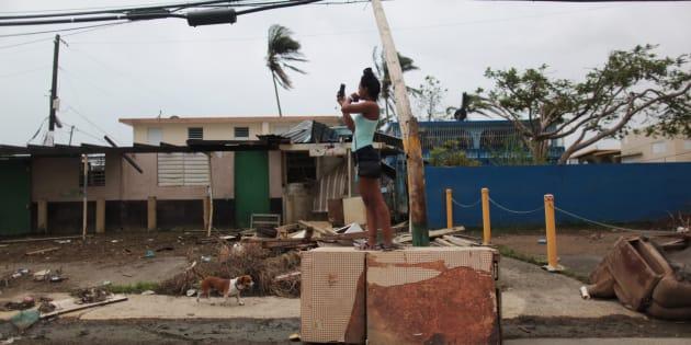 Une femme, debout sur un réfrigérateur, tente d'obtenir du réseau cellulaire, à Toa Baja, Porto Rico.