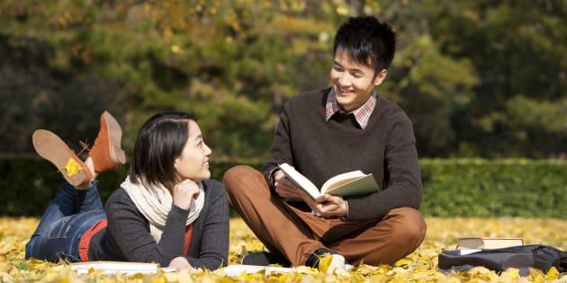 Jeune couple anonyme à Pékin, sur la pelouse d'un campus.