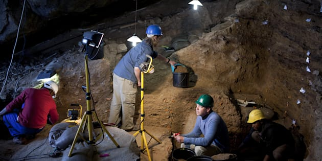 Dr. Curtis Marean (c) works with his colleagues inside a cave called PP13B on May 26, 2010, at Pinnacle Point near Mossel Bay South Africa.
