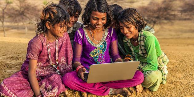 Happy Indian children, sitting on a sand dune and using laptop in desert village, Thar Desert, Rajasthan, India.