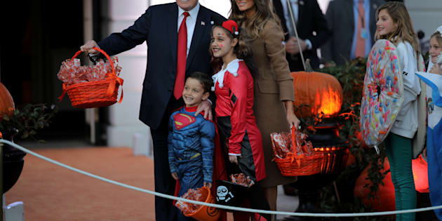U.S. President Donald Trump and First Lady Melania Trump pose for a picture as they give out Halloween treats to children from the South Portico of the White House in Washington, U.S., October 30, 2017. REUTERS/Carlos Barria