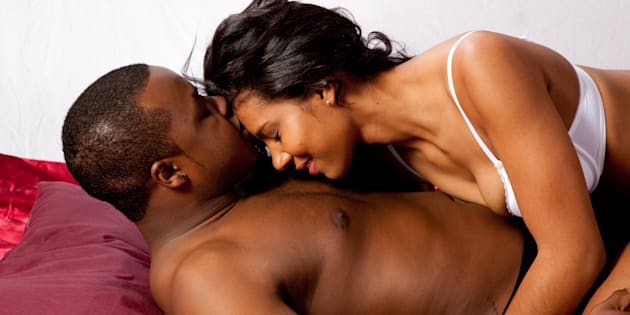 romantic black couple in their underwear, laying down together and kissing