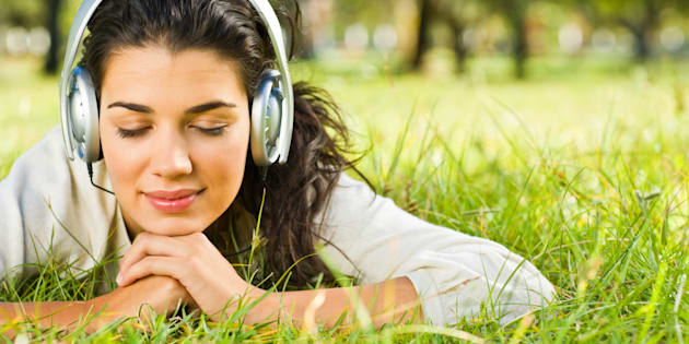 Smiling young woman listening to music at park