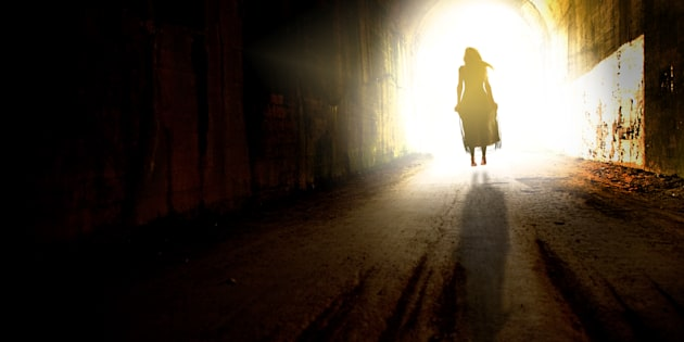 The figure of a woman in a dress floating to the light at the end of a tunnel.