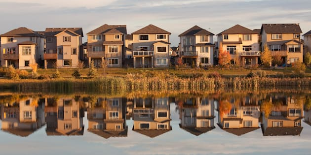 A row of houses reflected in a pond in Calgary, Alta.