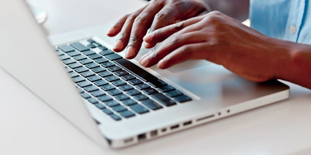 Close-up on male hands typing on laptop keyboard.