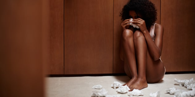 A crying woman sitting amidst the clutter of used tissues