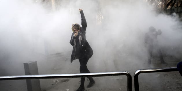 A university student attends a protest inside Tehran University while a smoke grenade is thrown by anti-riot Iranian police, in Tehran, Iran on Dec. 30, 2017.