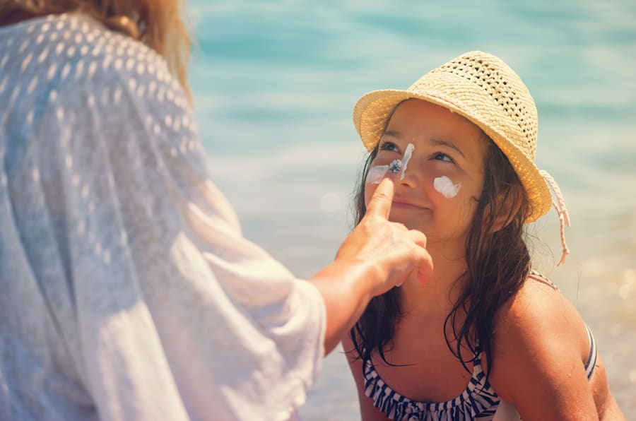 Young mother applying suntan lotion on daughter's face at the beach