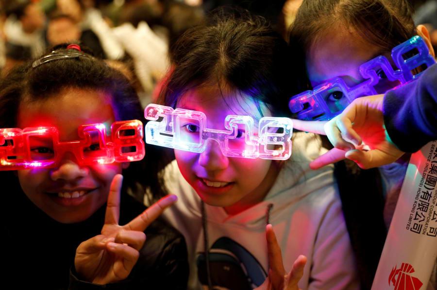 Crianças usam óculos temáticos para a chegada de 2018, em Hong Kong, na China.
