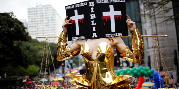 """Na Parada de 2016, a transexual Viviany Beleboni fez uma crítica à bancada evangélica no Congresso Nacional com fantasia que replicava uma Bíblia em que era possível ler: """"bancada evangélica"""" e """"retrocesso"""" estampados."""
