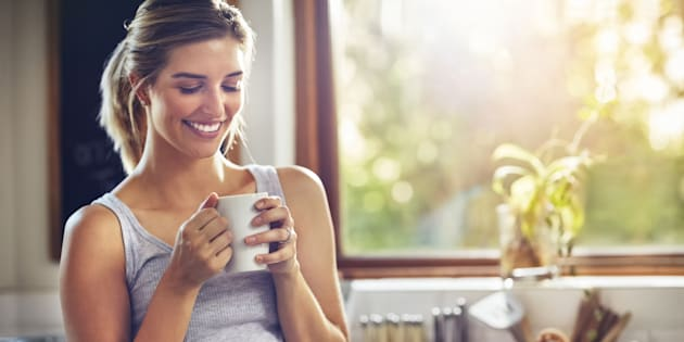 Shot of a young woman having her morning coffee