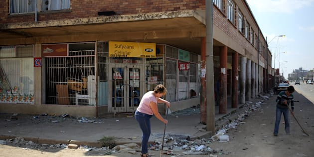 Locals clean up after over-night looting, when protesters took to the streets to demonstrate the killing of a boy in Coligny.