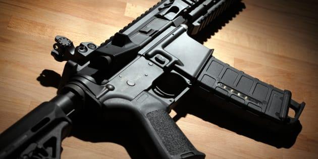 A modern custom AR-15 (M4A1) carbine is seen on a wooden surface.
