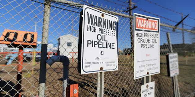 "Signs warning of the presence of oil pipelines are seen on a fence at ""Refinery Row"" outside facilities run by Enbridge, Kinder Morgan and Suncor in Sherwood Park near Edmonton, Alta."