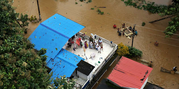 People wait for aid on the roof of their house at a flooded area in the southern state of Kerala, India, Aug. 17, 2018.