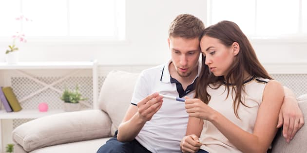 Sad couple after negative pregnancy test result, sitting on couch at home, copy space