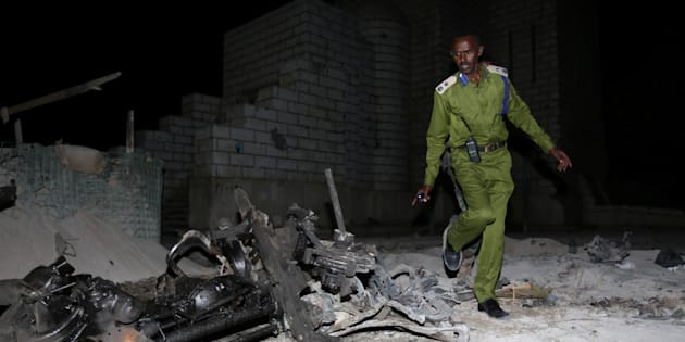 A Somali policeman inspects the scene of a suicide car explosion near the parliament in the capital Mogadishu, on Nov. 5, 2016.